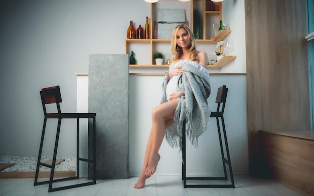Концепция - молодая красивая счастливая улыбающаяся беременная кавказская белокурая девушка, стоящая в гостиной белого света