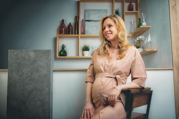 コンセプト-リビングルームの大きな腹を持つ若い美しい幸せな笑みを浮かべて妊娠中の白人ブロンドの女性