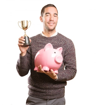 Concept of a young man saver holding a piggy bank and a cup