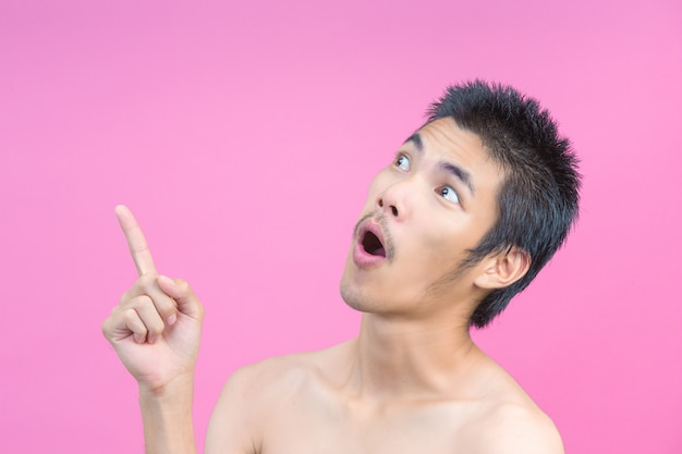 The concept of a young man without a shirt showing gestures and pink .