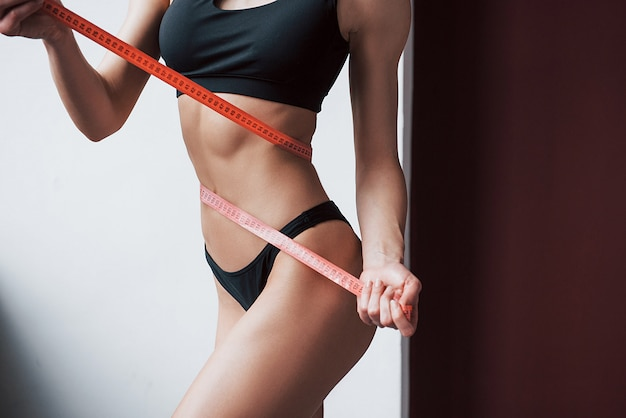 Conception of heathcare. close up view of young girl's fitness slim body measuring by the tape