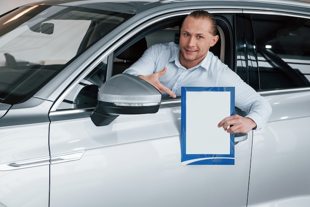 ビジネスの概念。紙とドキュメントを手にしてモダンな白い車に座っているマネージャー