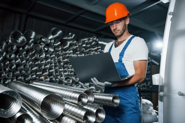 Концепция производства. мужчина в военной форме работает на производстве. современные промышленные технологии.