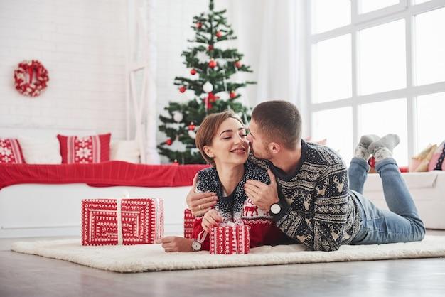 新年の概念。緑のホリデー ツリーのあるリビング ルームに横になっている素敵な若いカップル