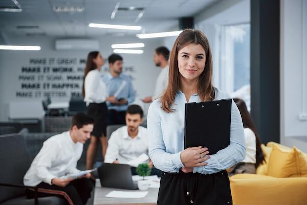 成功の構想。バックグラウンドで従業員とオフィスに立っている若い女の子の肖像画
