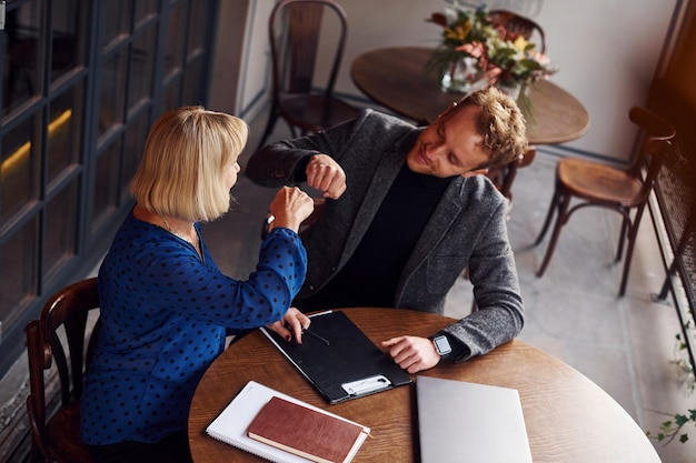 成功の概念。正装の若い男がカフェで老婆と商談。