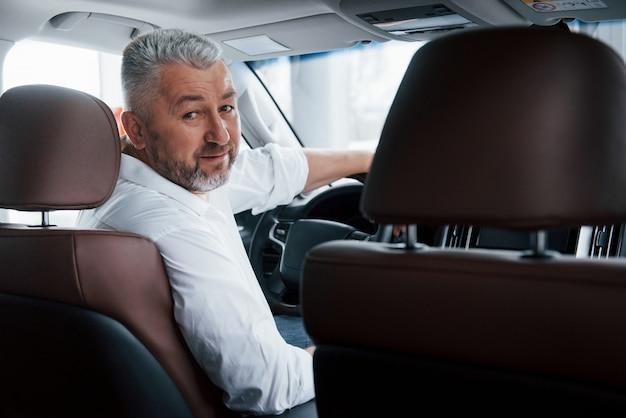Conception of success. joyful bearded man in white shirt looks back while sitting in the modern car