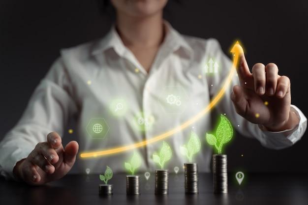経済技術の概念将来のビジネス環境にやさしい新しい取引プラットフォーム。コインスタックとホログラムチャートを持つビジネスマン。