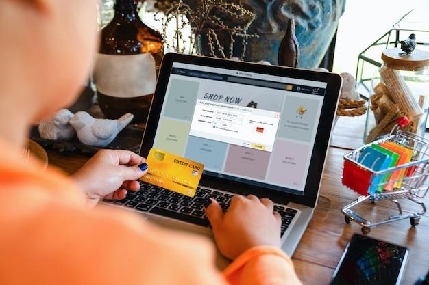 온라인 지불 전자 상거래 상점 보안 및 웹 상점의 개념 온라인 쇼핑 및 지불을 위해 노트북 컴퓨터 계정에 신용 카드 정보를 추가하는 아시아 여성