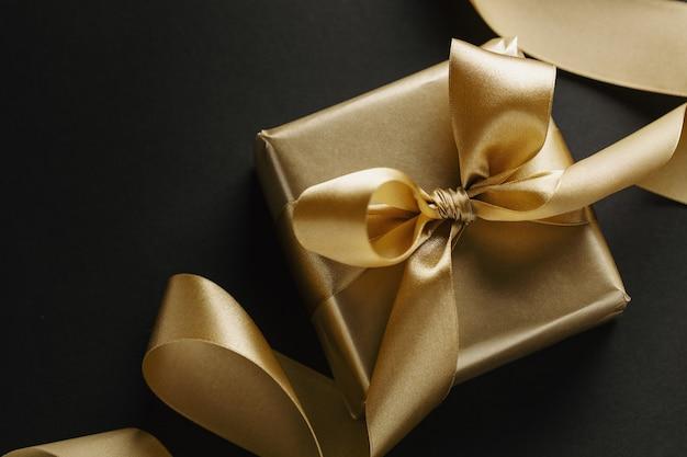 暗い上のリボンと金色の贈り物と概念的な背景。上面図