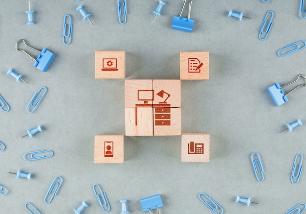 Conceptual of business office with wooden blocks with icons, paperclips, binder clips top view.