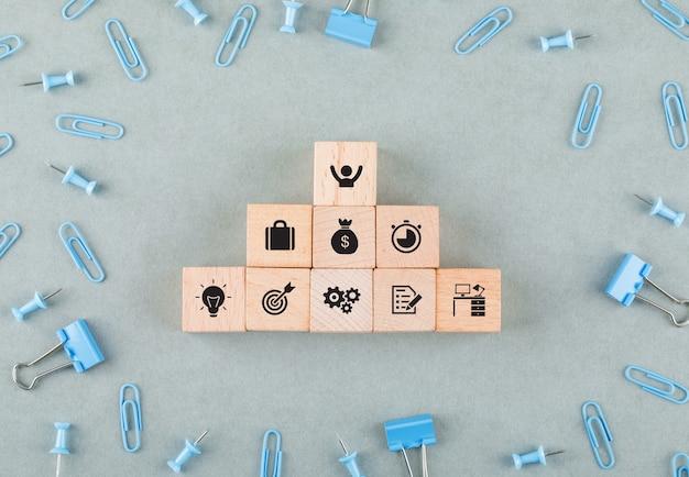 Concettuale di ufficio affari con blocchi di legno con icone, graffette, clip legante vista dall'alto.