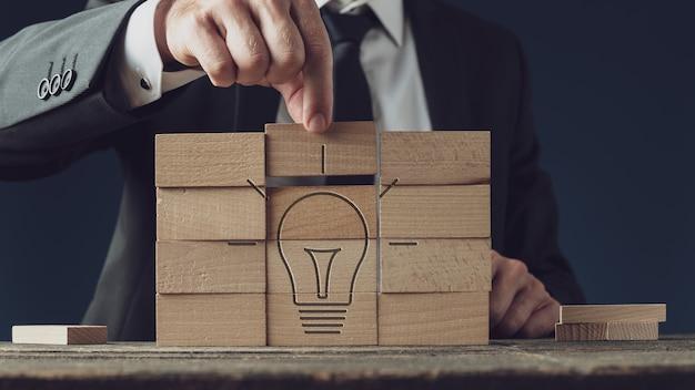 Концептуальное видение бизнеса и идея - бизнесмен, собирающий лампочку из деревянных колышков