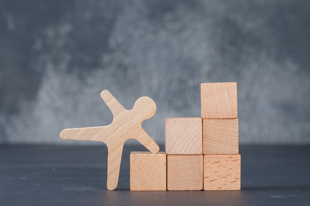 Conceptual of business with wooden blocks like stairs with wooden human figure.