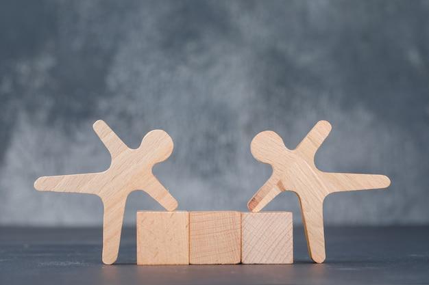 Concettuale di affari con blocchi di legno con figura umana in legno.