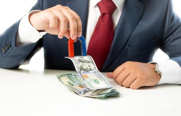 磁石を使ってテーブルの上のスタックからお金を引き出す概念的なビジネスマン