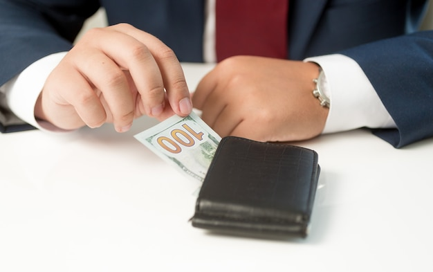 Conceptual businessman taking money from the wallet