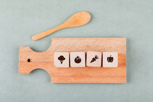 Conceptual of cooking with wooden blocks with icons, cutting board, wooden spoon top view.
