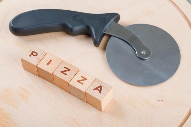 Concettuale di cucinare con blocchi di legno con parole, tagliapizza.