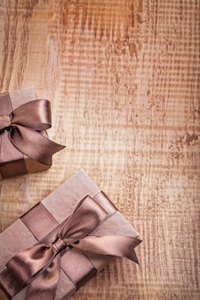 Conceptual copyspace photo two brown paper giftboxes with ribbons on vintage wooden board