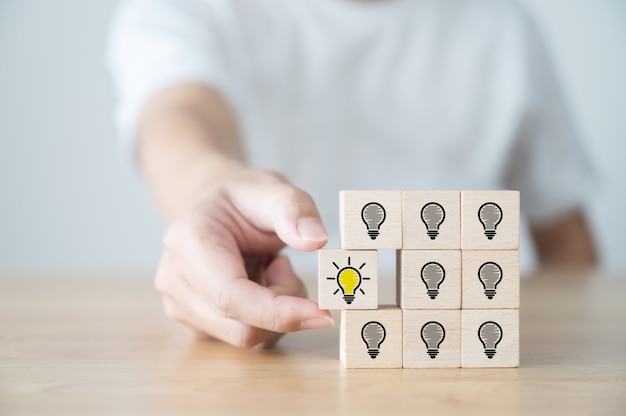 Conceptual of creative idea and innovation. hand picked wooden cube block with light bulb icon