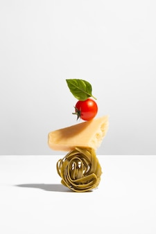 Conceptual creative still life with balancing food such as spaghetti nest, parmesan cheese, cherry tomato and green leaf on white background with shadow