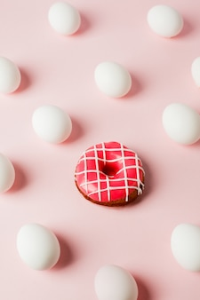 Conceptual easter egg background with pink donut on pink pastel background