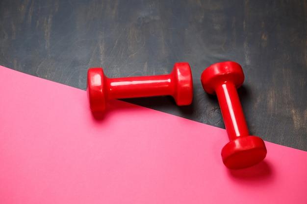 Концептуальный фитнес и здоровый спортивный фон с розовыми гантелями на розовом фоне. плоский вид сверху с копией пространства.