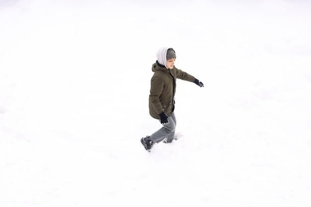 Conceptual image of boy runnin lying down on the ground covered with snow isolated on white, top view from drone