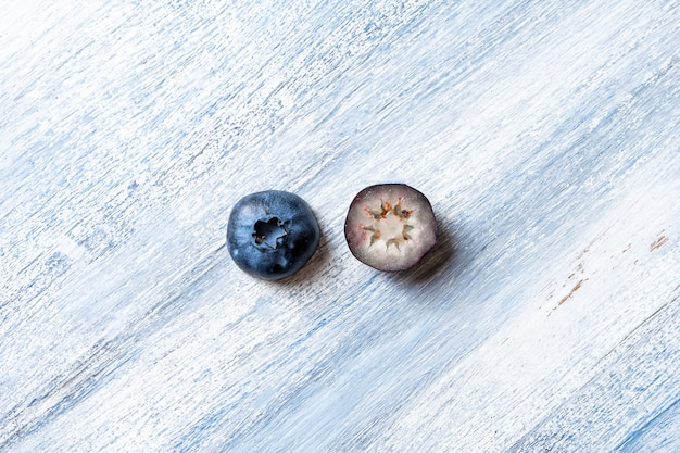 Conceptual image of eyes made from blueberry. vitamins for vision. free copy space. flat lay. creative layout with summer fruit. blueberry minimalism pattern on blue background. pharmacology