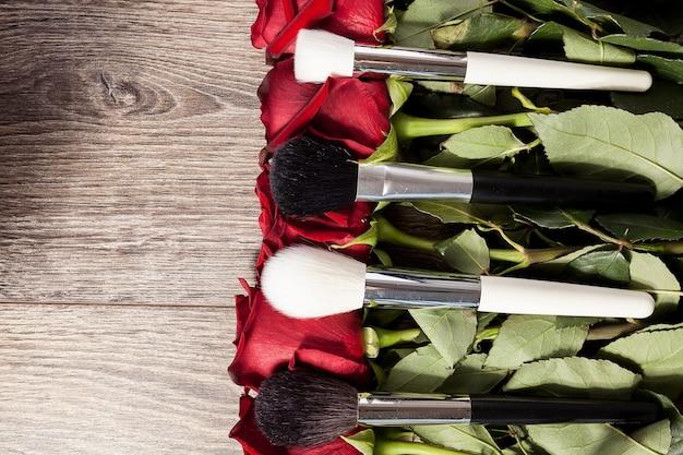 Immagine concettuale di pennelli per il trucco accanto a rose su fondo in legno