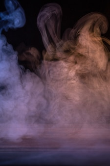 Conceptual image of multi-colored smoke isolated on dark black background and wooden table.