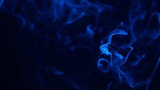 ダークブラックに分離された青い色の煙の概念的なイメージ
