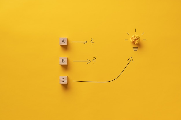 ブレーンストーミングと黄色の背景の上の電球とアイデアの概念的なイメージ。