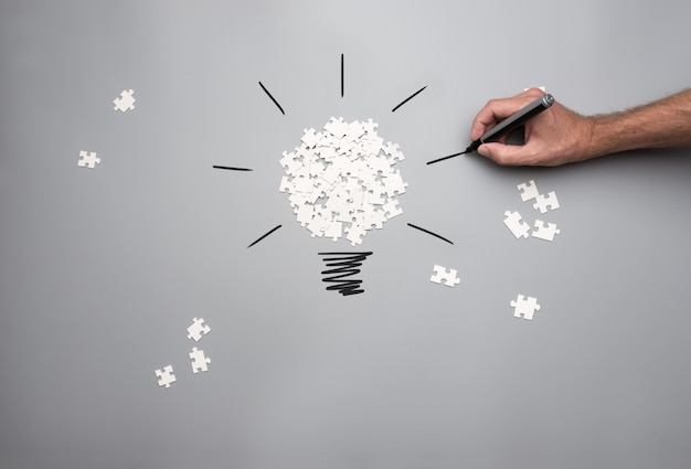 전구를 형성하는 흰색 흩어져 퍼즐 조각 더미와 함께 사업 비전과 아이디어의 개념적 이미지
