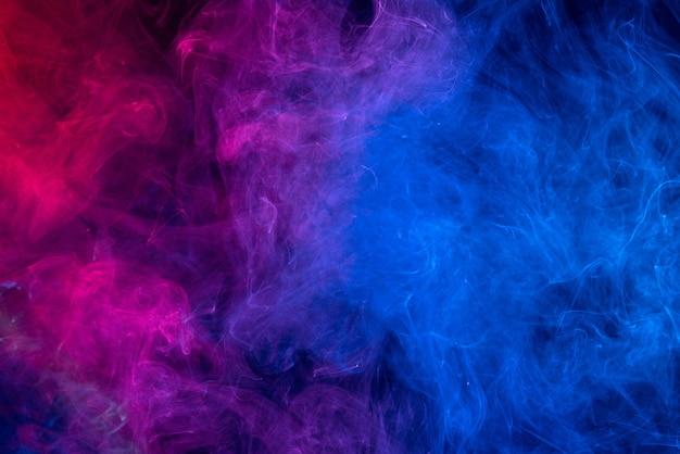 暗い黒の背景、ハロウィーンのコンセプトデザイン要素に分離されたカラフルな赤と青の色の煙の概念的なイメージ。