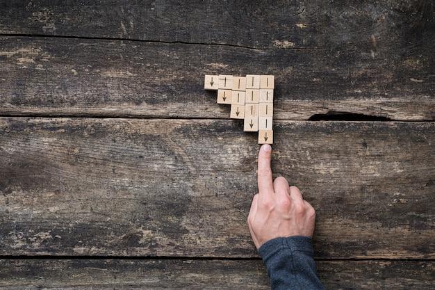 ビジネス不況-下向きの矢印を停止する男性の指との戦いの概念図。
