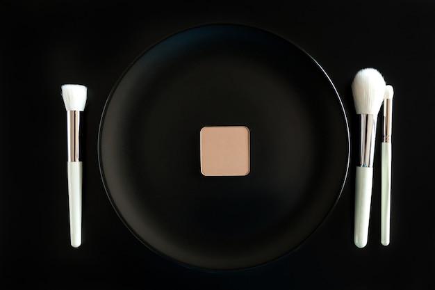 검정색 배경에 있는 저녁 접시 옆에 있는 메이크업 브러쉬의 개념적 이미지