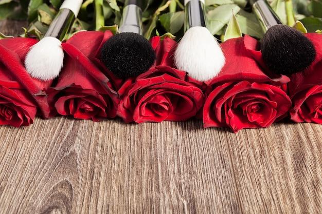 木製の背景の上のバラの横にある化粧ブラシの概念的なイメージ