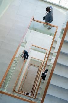 オフィスの階段の吹き抜け、階段のらせん状の構成の上を移動する現代のビジネスマンの概念的なイメージ