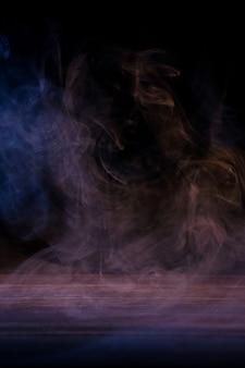 濃い黒の背景と木製のテーブルに分離されたマルチカラーの煙の概念的なイメージ。