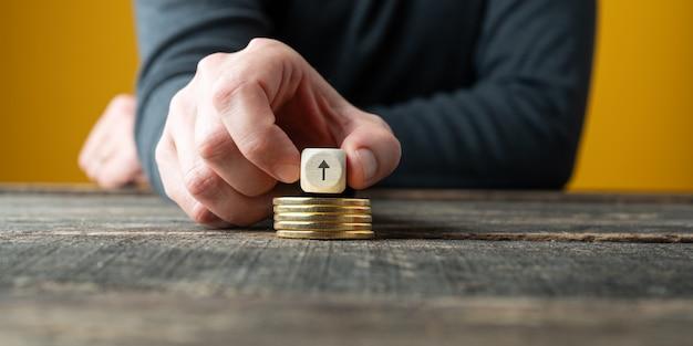 Концептуальное изображение роста фондового рынка - стрелка вверх на стопке золотых монет.