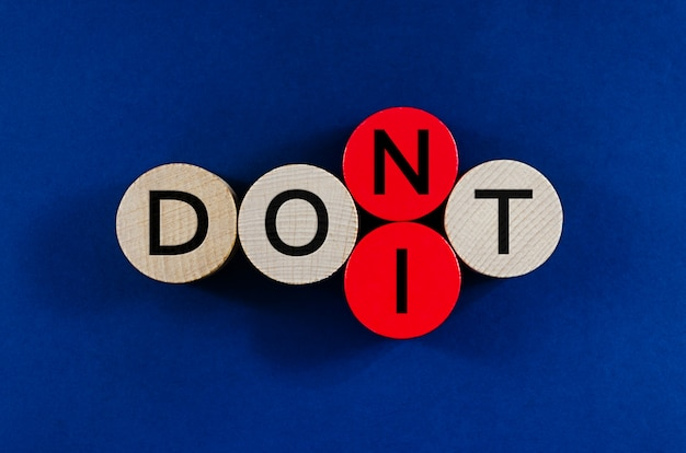 Conceptual image of word dont spelled on wooden pegs with second to the last circle replacing to spell the word do it.