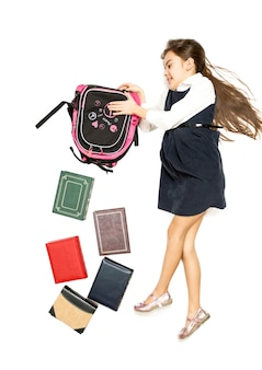 Conceptual isolated photo of cute schoolgirl emptying backpack full of books