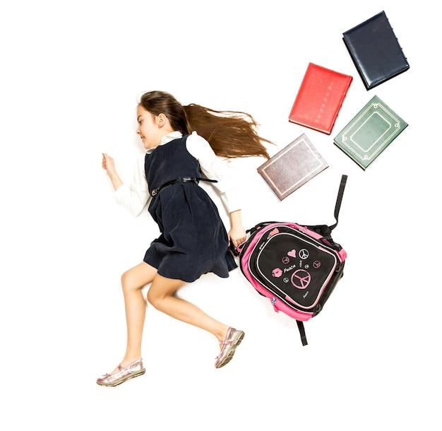 Концептуальные изолированные фото милой школьницы, бегущей в школу с рюкзаком