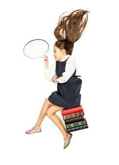 Концептуальные изолированные фото милой вдумчивой школьницы, сидящей на книгах