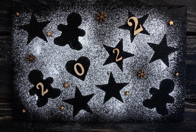 Концептуальная новогодняя композиция в форме звездочек сердца и пряничного человечка2022 flat lay
