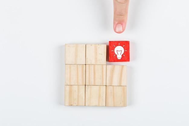 아이디어를 가리키는 아이디어 손의 개념입니다. 흰색 배경 평면도에 나무 블록으로. 가로 이미지