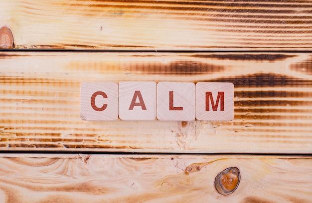 Концептуальные мотивации с деревянными блоками с набранным на нем спокойствием на плоской планировке деревянного стола.