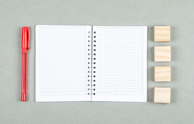 Conceptual of open notebook and taking note. with pen, wooden blocks on gray background top view. space for text horizontal image